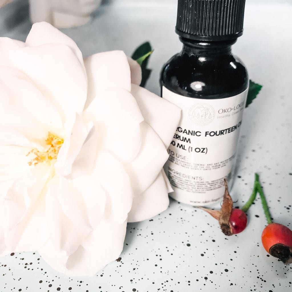 bottle of serum and white rose