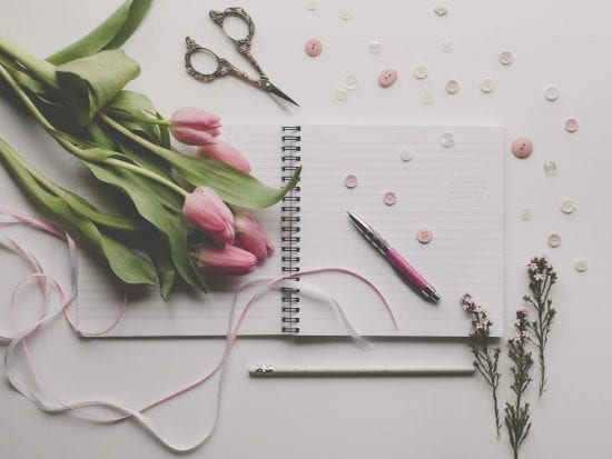 journal, pen, and tulips journaling as one of the stress copying strategies