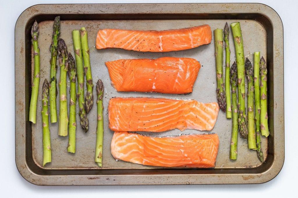 wild Alaskan salmon fillet on baking dish with asparagus