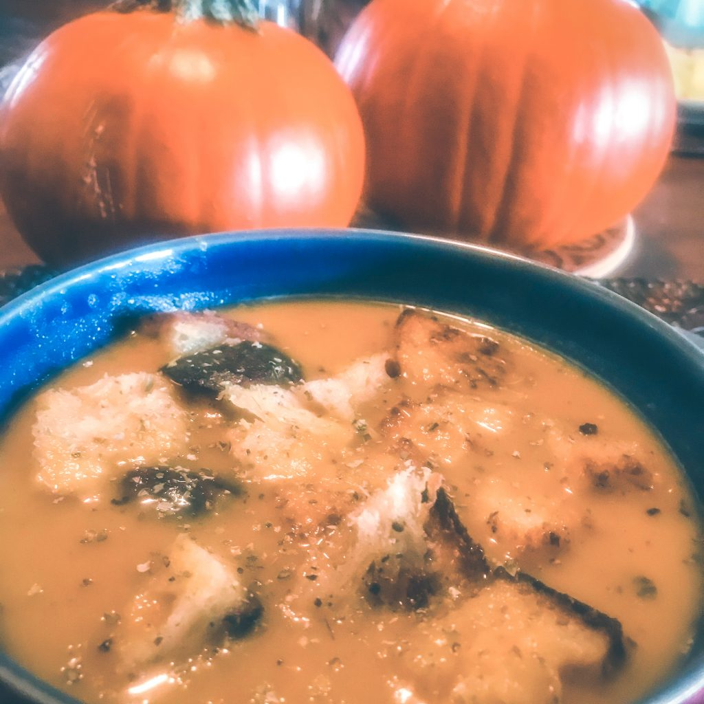 cozy fall soup with pumpkins in the background