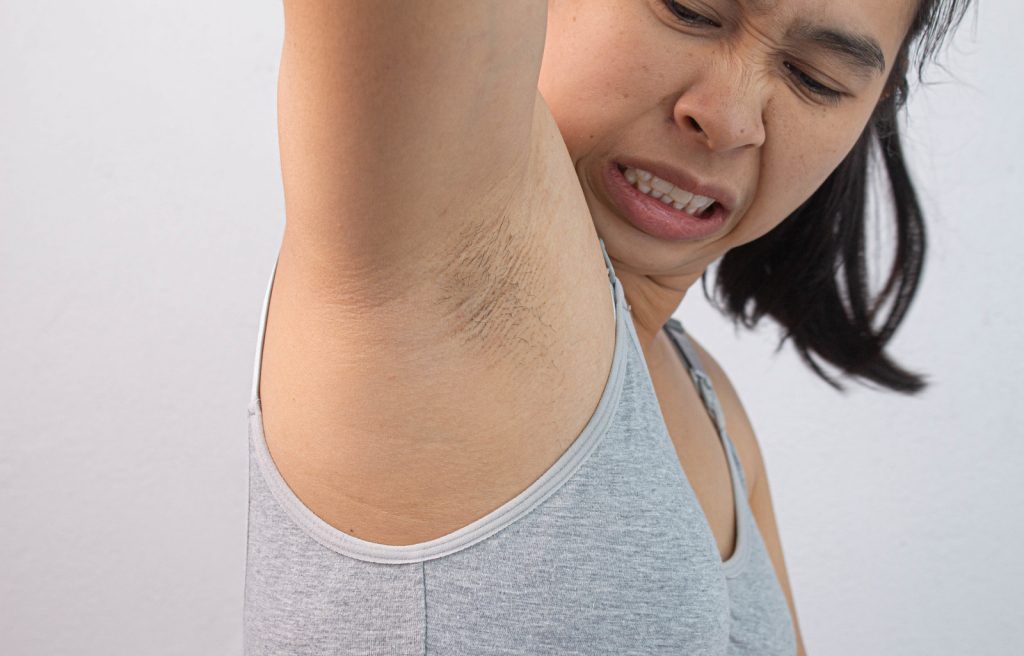 woman smelling her armpits